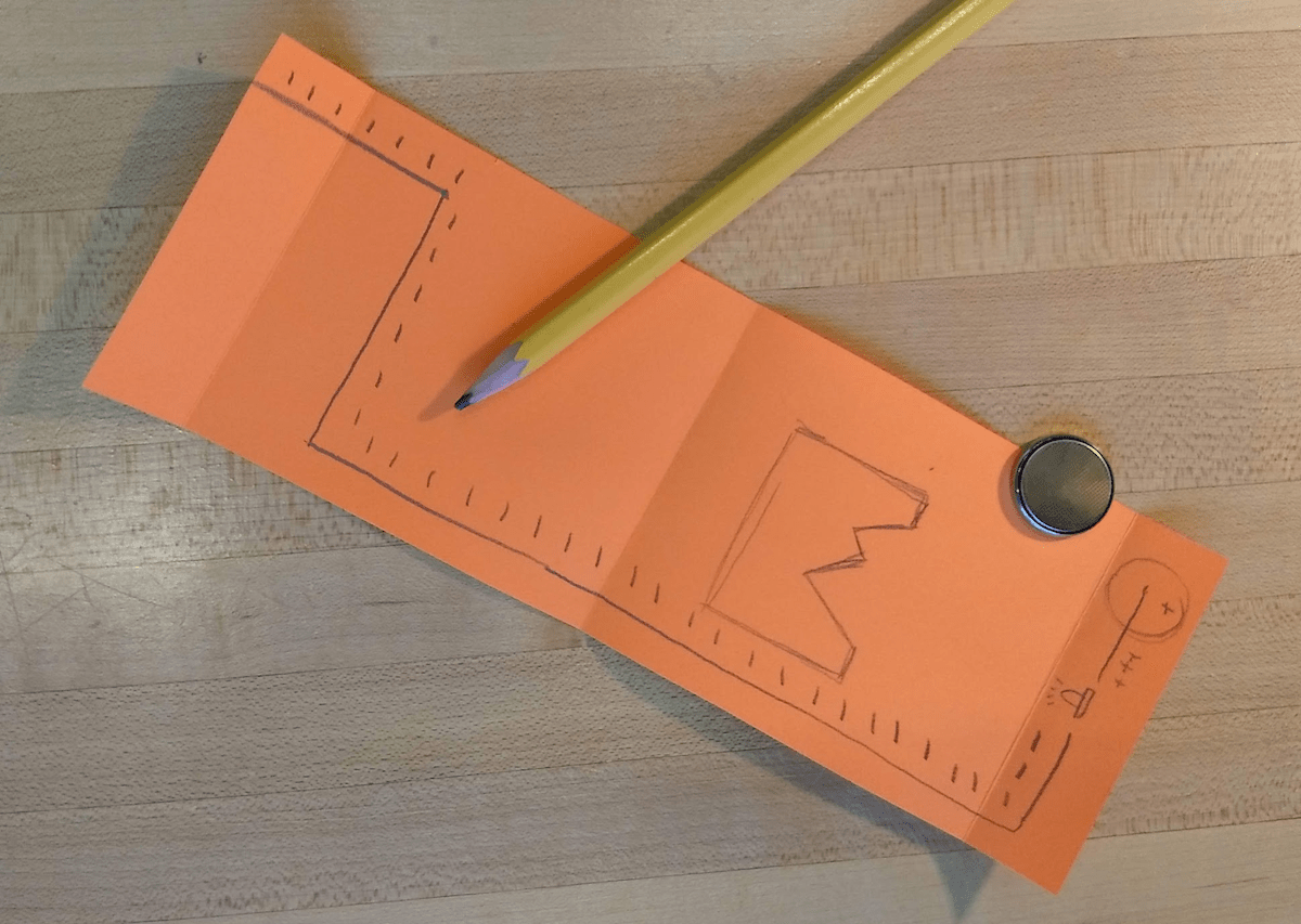 Draw your shadow box design and the circuit. Note that the battery will be sandwiched between the two ends of the paper (which you'll see below). Cut out your shadow box design with an x-acto knife.