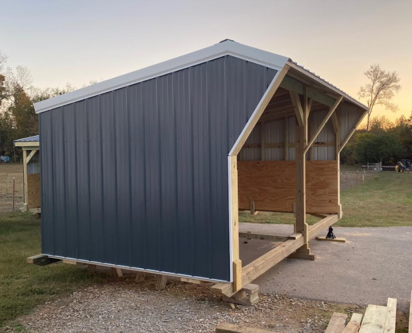 10' x 18' with 9' peak, charcoal blue with white trim and galvalume roof.